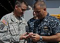 US Navy 100224-N-0808P-009 Maj. Gen. Daniel B. Allyn, deputy commander of Joint Task Force Haiti, left, presents a command coin to Cmdr. George Doyon, commanding officer of the amphibious transport dock ship USS Carter Hall (LS.jpg