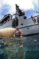 US Navy 100820-N-9769P-014 Navy Diver 2nd Class Mario Nicoletti, assigned to Company 2-6 of Mobile Diving and Salvage Unit (MDSU) 2, attaches a safety line to a salvage project that was brought to the surface using lift bags.jpg