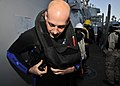 US Navy 101128-N-6499D-017 Interior Communications Electrician 1st Class Jonathon Grinols dons a life preserver before a security patrol aboard USS.jpg