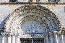 Vue d'un arche surmontant un portail de pierre.