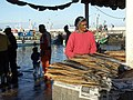 Woman smoking a cigarette behind a fish stall in South Africa.jpg