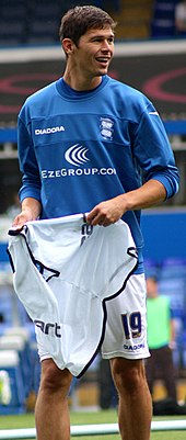 A dark-haired white man wearing a blue training top and white shorts.