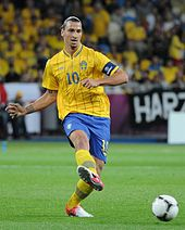 Zlatan Ibrahimović wearing a yellow shirt and blue shorts, passing the ball