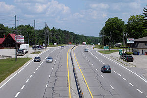 Right-in/right-out - King's Highway 11, looking north from overpass, toward South Sparrow Lake Road/Goldstein Road in Severn, Ontario, Canada. Several characteristics of a RIRO expressway are shown in the image: there is an unbroken median, there are right-in/right-out turns at the side roads, there are businesses with direct right-in/right-out frontage along the highway, and there is a sign indicating that access to the southbound lanes of the highway is via a right turn onto the side road (in this case, by following Goldstein Road to the overpass road, crossing over the highway, then continuing on the overpass road to South Sparrow Lake Road).