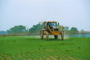 Pesticide application - Self-propelled row-crop sprayer applying pesticide to post-emergent corn