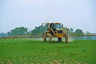 Pesticide application - Self-propelled row-crop sprayer applying pesticide to post-emergent corn