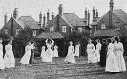 A group of 15 women in long-sleeved shirts and ankle-length skirts on a grass netball court