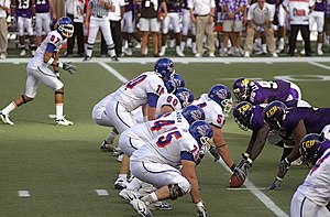 Lineman (gridiron football) - Offensive line in three-point stance in white.