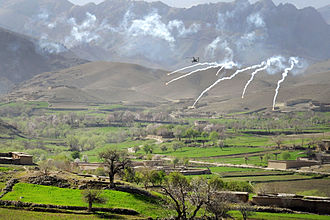 Daykundi Province - An AH-64 Apache helicopter shoots flares over a valley while operating in support members of the 8th Commando Kandak and coalition special operations forces during a firefight near Nawa Garay village, Kajran district in April 2012.