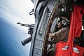 A Sailor mans a .50-caliber machine gun inside an MH-60S Sea Hawk helicopter. (28123550458).jpg