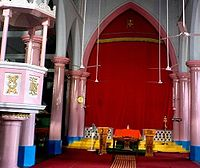 A Syro-Malabar Catholic Church in Kerala, with the Holy of Holies containing the Nasrani Menorah or Mar Thoma Sliba (St. Thomas Cross) veiled by a red curtain in the tradition of ancient Jewish synagogue.