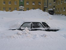 A car buried in a snowdrift with only the left side, from just below the windows, visible