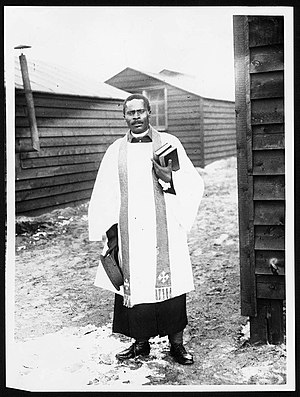 South African Native Labour Corps - African priest, Western Front. He wears what seem to be Church of England vestments over army uniform. He is standing in a camp of wooden huts, probably one of the segregated camps of the South African Native Labour Corps (National Library of Scotland 4687906729)