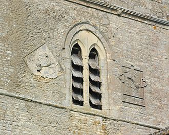 Ambrosden - St Mary the Virgin parish church: belfry opening and pargetted panels on the east side of the tower. The panel on the left shows a lion; that on the right was made in 1587, restored in 1892 and seems to show a griffin.