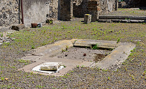 Impluvium - Impluvium in the center of the atrium of a former house, ancient Roman Pompeii, Campania, Italy. The drain into the underground cistern is visible.