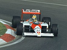 Photo of Ayrton Senna driving a red and white McLaren on a race track