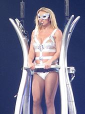 Britney Spears performing onstage, standing on a fence like contraption.