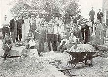 A wheelbarrow full of debris sits in the foreground, while townspeople and workers look at the unknown photographer, apparently taking a break from cleaning up debris after the bombing at the school