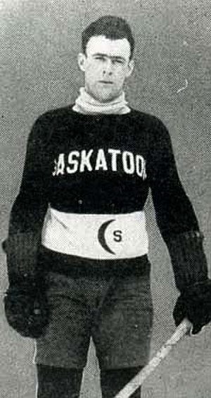 "Bill Cook - A young man with short, dark hair in a hockey uniform.  His sweater is dark with the word ""SASKATOON"" written across the chest and a white stripe at the stomach with a crescent symbol"