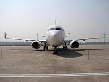A white aircraft with green winglets parked on the ramp showing a front view