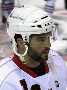 Photographie couleur d'un homme, barbu, de 3 quarts profil, portant un casque de hockey sur glace.