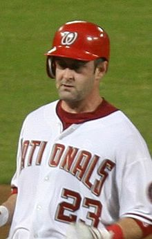A man wearing a white baseball jersey and red batting helmet with a look of concentration upon his face