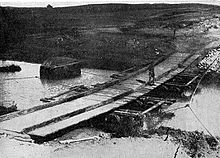 The bridge was constructed by the New Zealand Mounted Rifles Brigade. Long planks of wood were laid across the stream on empty wine casks; shorter planks were then laid on top crosswise to form a flat surface.