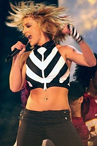 A blond female performer in a black-and-white ensemble, holding a microphone near her mouth.