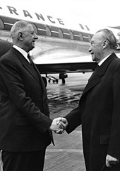 De Gualle and Konrad Adenauer shake hands in front of a plane.
