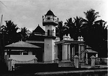 A black and white picture of a mosque with palm trees in the background