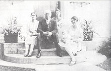 A man and three women seated on the front stoop of a house. One of the women is cradling a baby.