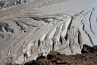 Shear or herring-bone crevasses on Emmons Glacier (Mount Rainier); such crevasses often form near the edge of a glacier where interactions with underlying or marginal rock impede flow. In this case, the impediment appears to be some distance from the near margin of the glacier. Chevron Crevasses 00.JPG