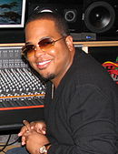 An African American man wearing glasses, sits smiling in a recording studio.