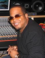 Un homme afro-américain portant des lunettes de soleil orange et un T-shirt noir sourit.