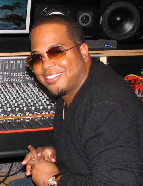 An African-American man wearing orange sunglasses and black T-shirt is smiling.