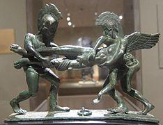 Statue en bronze de deux soldats avec casques à crête et armures, en train de se disputer un corps.