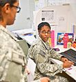 Courtney Drinks, with the Joint Task Force Joint Troop Clinic, briefs Dana Ugwu, a field surgeon and care provider.jpg