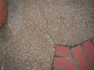 Stress concentration - The sharp corner at the brick has acted as a stress concentrator within the concrete causing it to crack