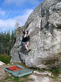 A climber with a crash pad on the ground.(Saint Just, Cantal, France)