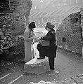 Dame (Nell Langlais) kijkt naar een camee die door de verkoper tegen het licht , Bestanddeelnr 191-1236.jpg
