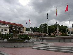 An ornate fountain at left with steps leading up to a wall with some of Malaysia's state flags on it.