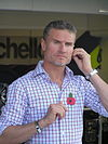 David Coulthard wearing a checkered T-shirt preparing for a media broadcast