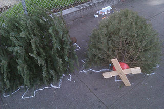 Here lie two 'Christmas trees' discarded on pavement, given chalk outlines by activists, as a murder scene - image via Wikimedia Commons.