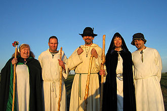 Druidry (modern) - A group of druids of the Order of Bards Ovates and Druids in the early morning glow of the sun, shortly after having welcomed the sunrise at Stonehenge on the morning of the summer solstice.