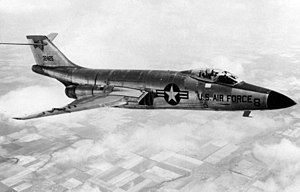 Black-and-white photo of jet aircraft flying right above clouds. On the aircraft's side is a symbol with a star, to the right of which says U.S. Air Force. Its horizontal stabilizers are located atop its fin.
