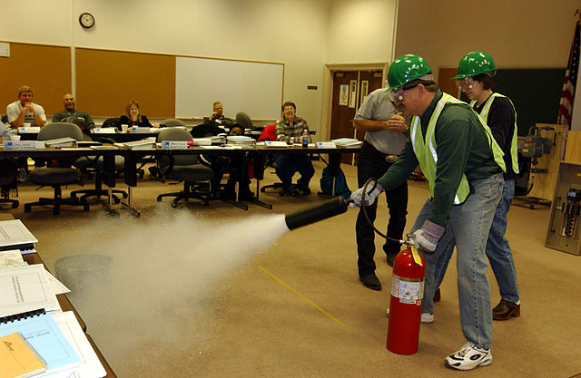 A CERT volunteer practices using a fire extinguisher