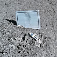 A silvery human figure, apparently face down, in front of a metallic plaque with a list of names on a dusty gray surface