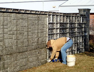 Fence - Concrete fence constructed with an ashlar texture.