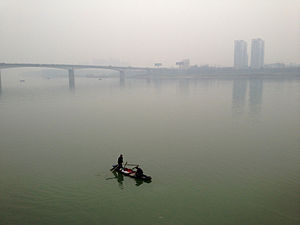 Changde - Two fishermen on the Yuan river in downtown Changde. The bridge and Jiangnan district can be seen in the background.