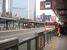 Passengers and a bus at a station